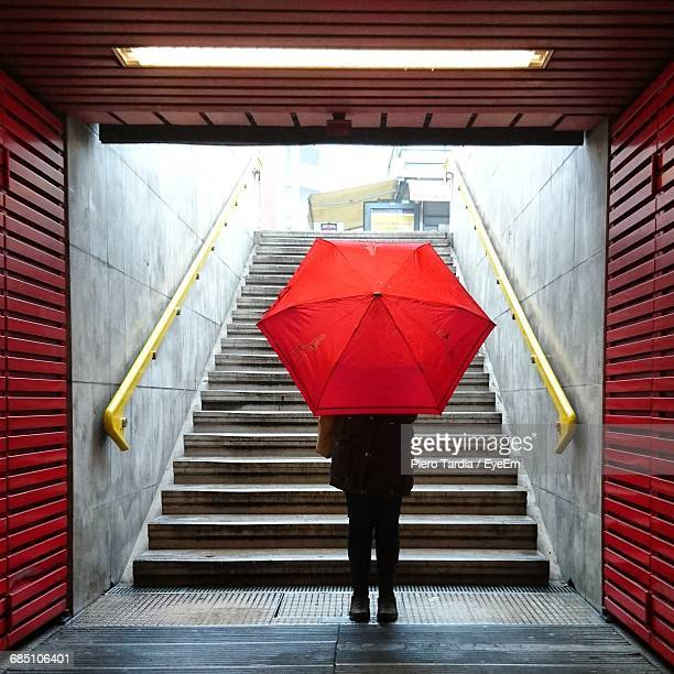 Rear View Of Woman With Red Umbrella Standing In Underground Walkway