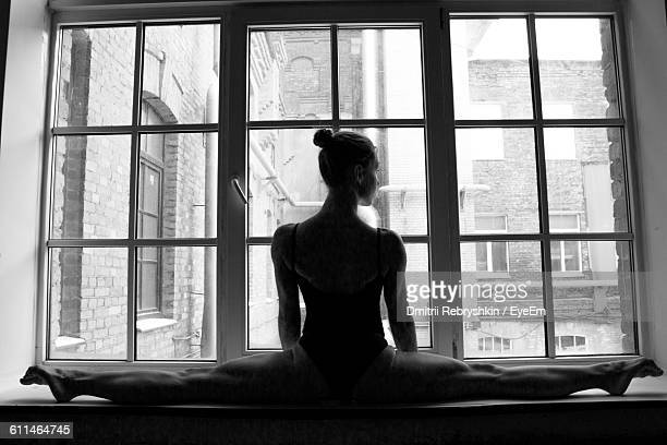 Rear View Of Woman With Split On Window Sill