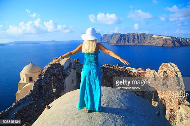 Rear view of Woman with turquoise dress in Santorini, Greece.