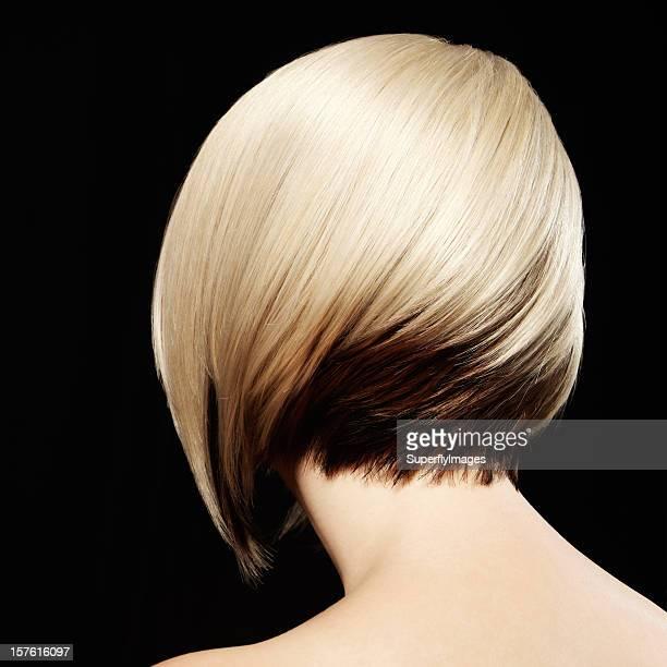 Rückansicht der Frau mit zweifarbigen Frisur. Schwarzem Hintergrund.