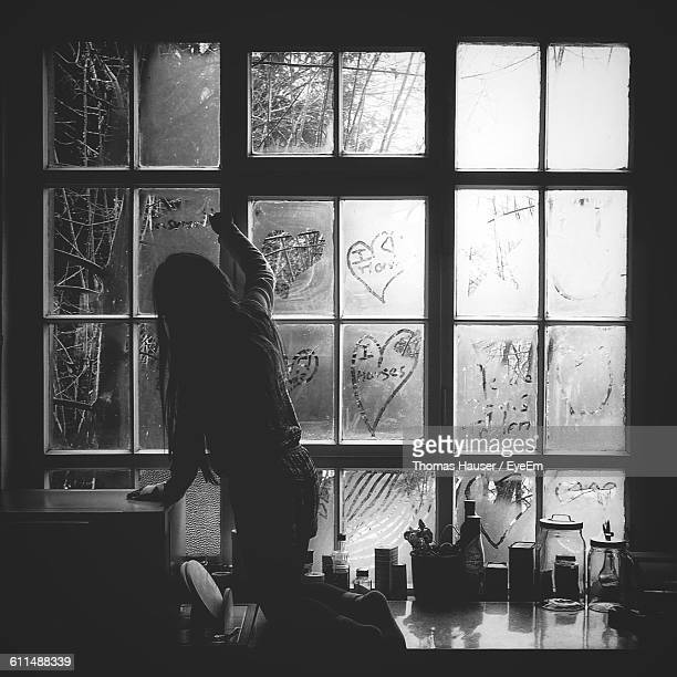 Rear View Of Woman Writing On Old Glass Window