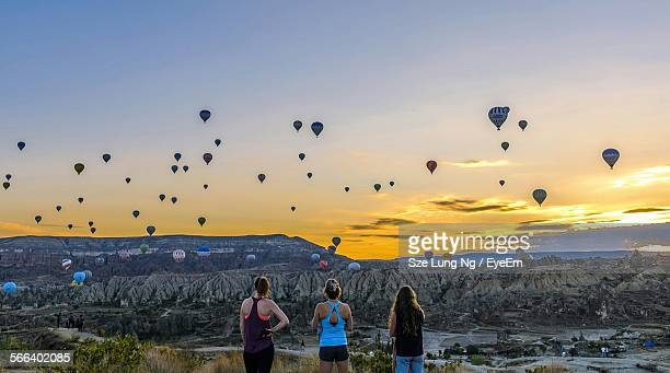 Rear View Of Women Against Hot Air Balloons In Mid-Air During Sunrise In Goreme