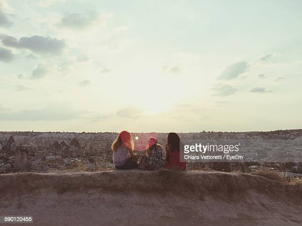 Rear View Of Women Sitting At Cappadocia Against Sunset Sky