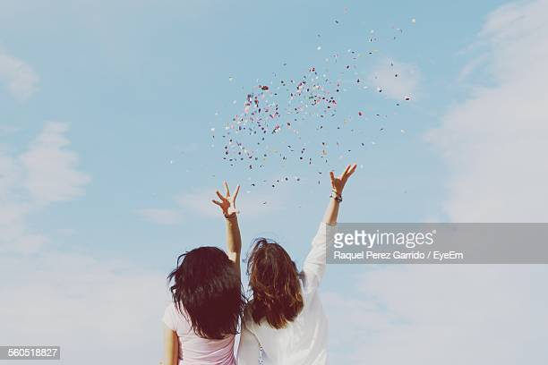 Rear View Of Women Throwing Confetti Against Sky