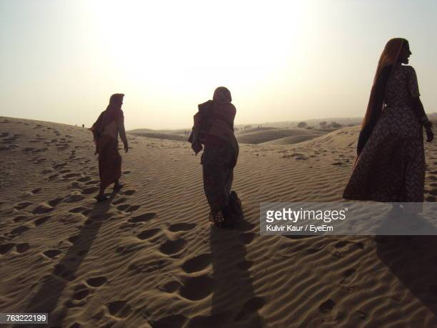 Rear View Of Women Walking On Sand Dune Against Clear Sky