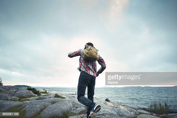 Rear view of wonderlust man jumping on rocks by sea against cloudy sky