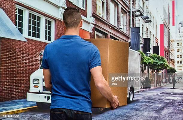 Vue arrière du travailleur tenant la boîte en plein air
