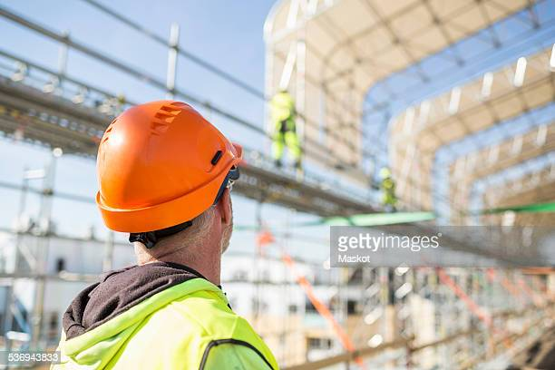 Rear view of worker looking at colleagues working at construction site