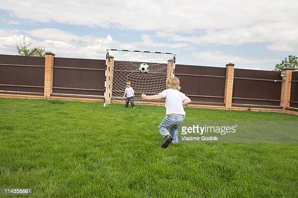 rear view of young boy kicking football into goal
