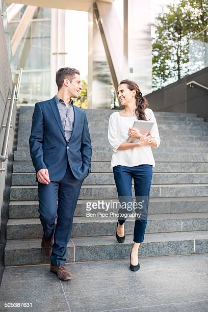 Rear view of young businessman and woman walking down stairway, London, UK