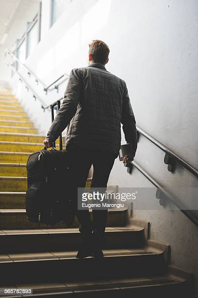Rear view of young businessman commuter on stairs carrying suitcase.