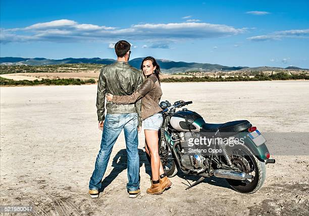 Rear view of young couple and motorcycle on arid plain, Cagliari, Sardinia, Italy