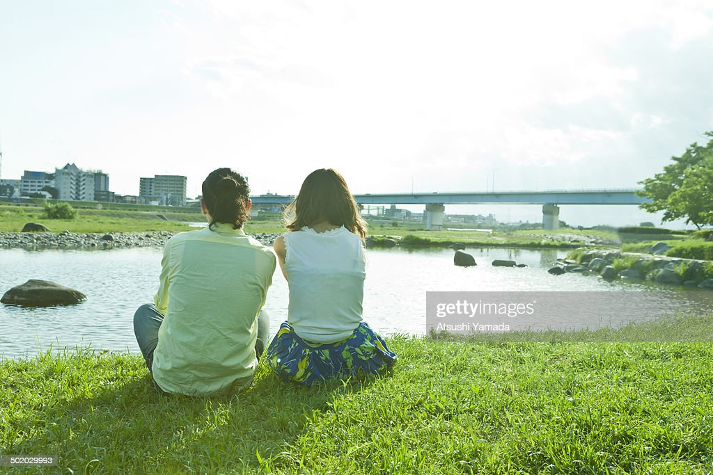 Rear view of young couple beside river