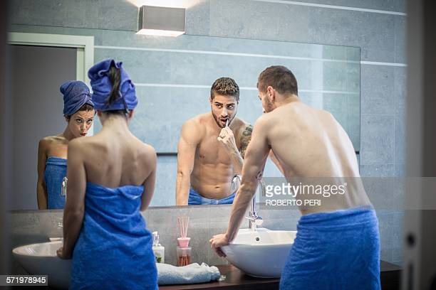 Rear view of young couple brushing teeth in bathroom mirror