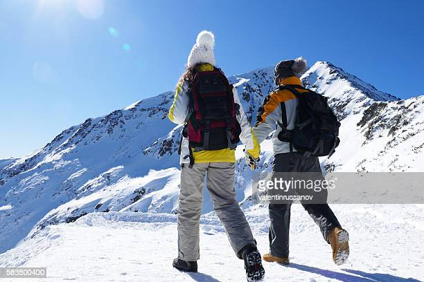 Rear view of young couple climbing up on mountain