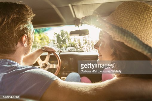 Rear view of young couple driving car