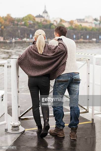 Rear view of young couple leaning on railing outdoors