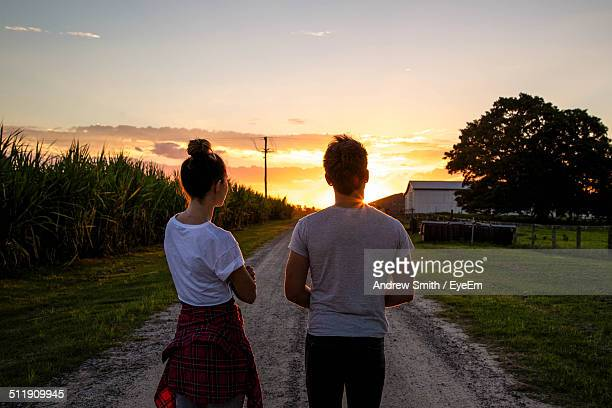 Rear view of young couple standing on dirt road at sunset