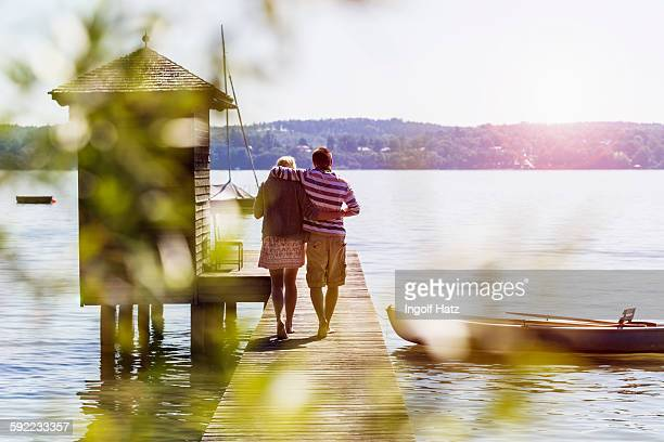 Rear view of young couple walking along pier on lake to boathouse, Schondorf, Ammersee, Bavaria, Germany