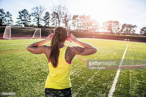 Rear view of young female athlete putting on head phones on sports field