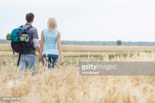 Rear view of young hiking couple walking through field : Stock-Foto