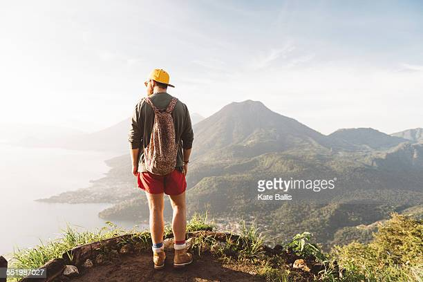 Rear view of young man looking out over Lake Atitlan, Guatemala