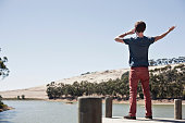 Rear view of young man on mobile phone, overlooking lake scene