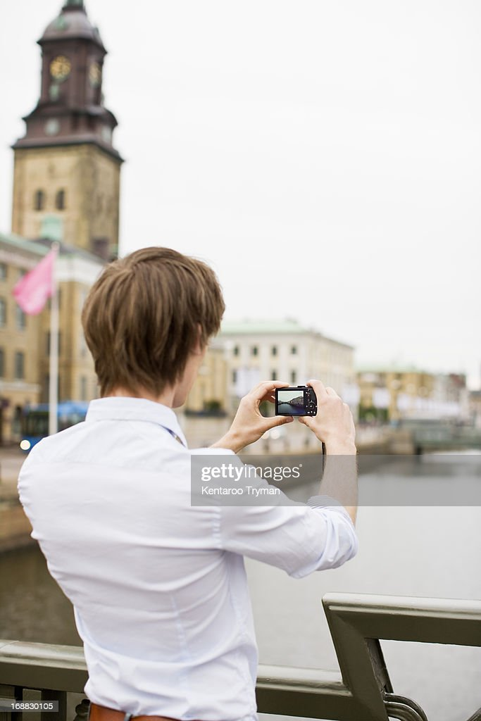 Rear view of young man photographing buildings : Stock Photo