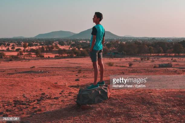 Rear View Of Young Man Standing On Rock Over Field Against Sky