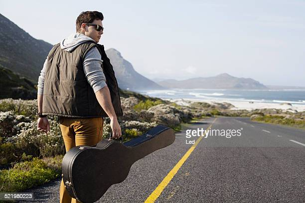 Rear view of young man walking on coastal road carrying guitar case, Cape Town, Western Cape, South Africa