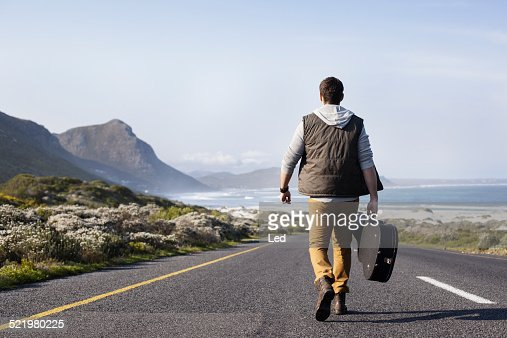Rear view of young man with guitar case walking on coastal road, Cape Town, Western Cape, South Africa