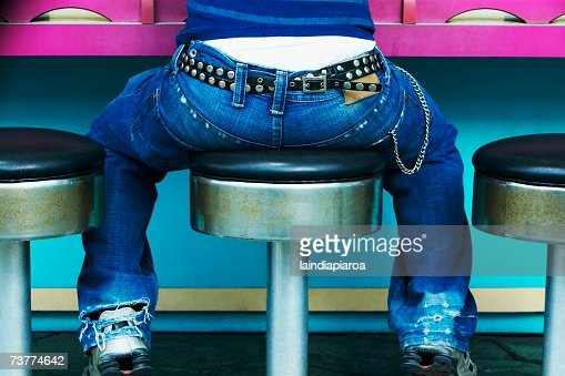 Rear view of young person with studded belt sitting on stool at counter : Stock Photo