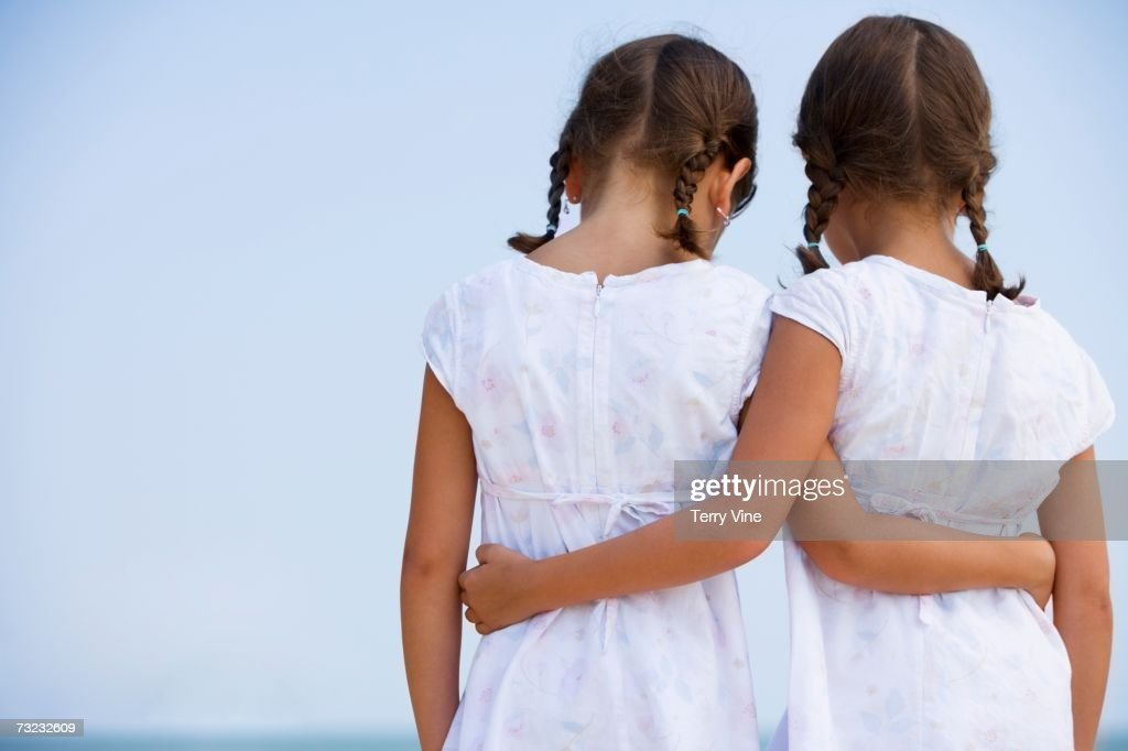 Rear view of young sisters wearing matching dresses and hugging outdoors : Stock Photo