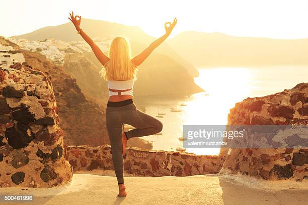 Rear view of young woman at sunset in Santorini Greece
