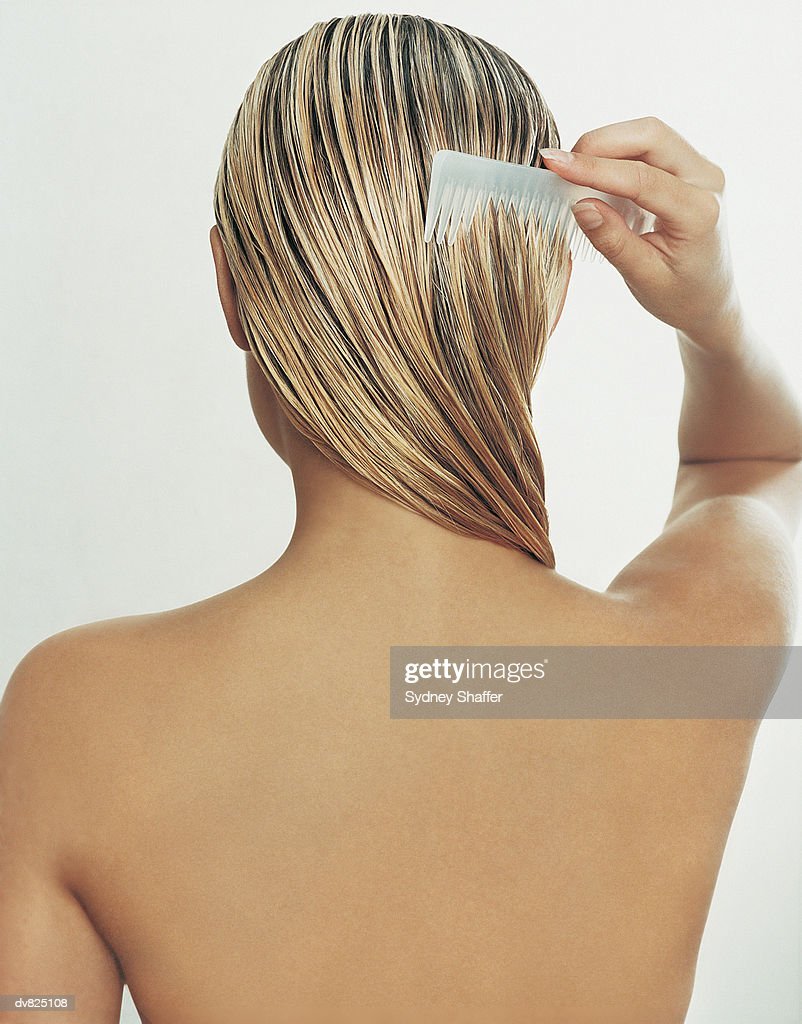 Rear View of Young Woman Brushing Her Hair : Stock Photo