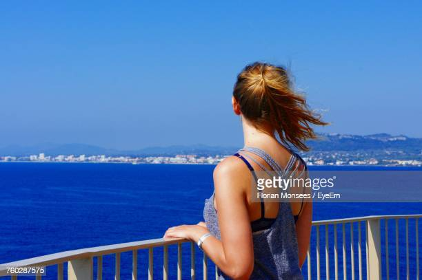 Rear View Of Young Woman By Railing Looking At Sea On Sunny Day
