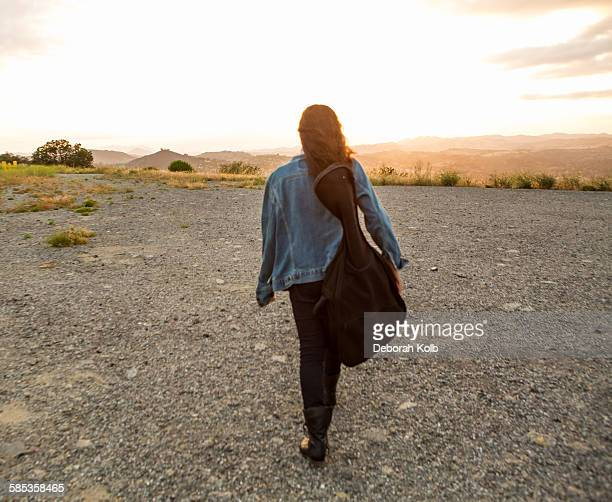 Rear view of young woman carrying guitar case at sunset