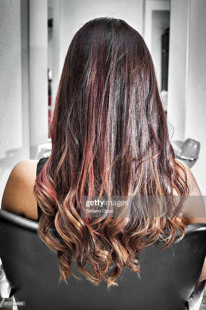Rear view of young woman in hair salon with long brunette hair with waves and pink highlights