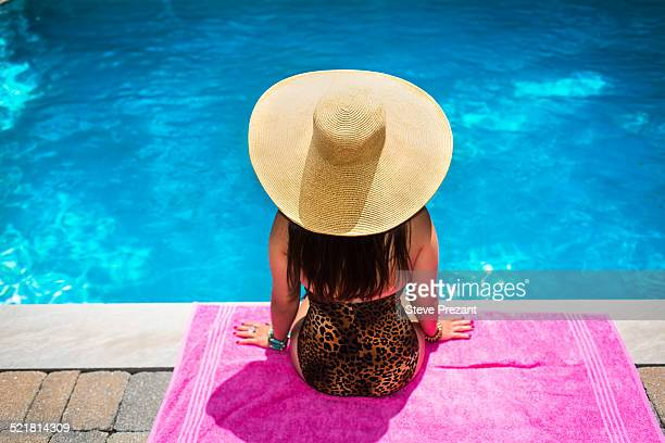 Rear view of young woman in sunhat sitting at poolside