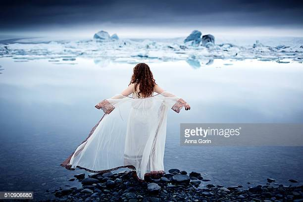 Rear view of young woman in vintage sheer white nightgown standing at edge of Jokulsarlon glacial lagoon, arms outstretched