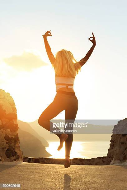 Rear view of young woman jumping in Santorini Greece