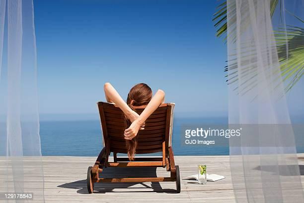 Rückansicht der jungen Frau auf deck chair