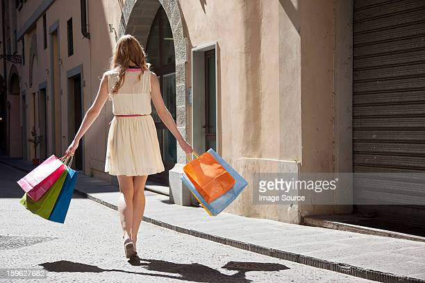 Rear view of young woman on street with shopping bags