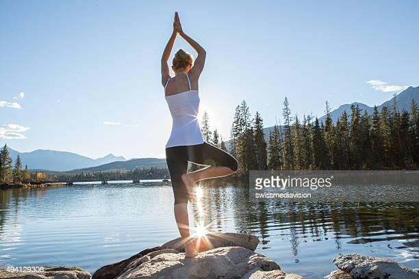 Vue arrière du jeune femme pratiquant yoga par le lac