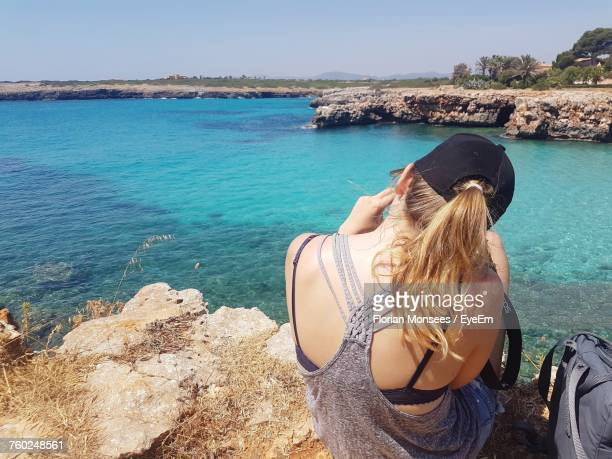 Rear View Of Young Woman Sitting On Rock Against Sea
