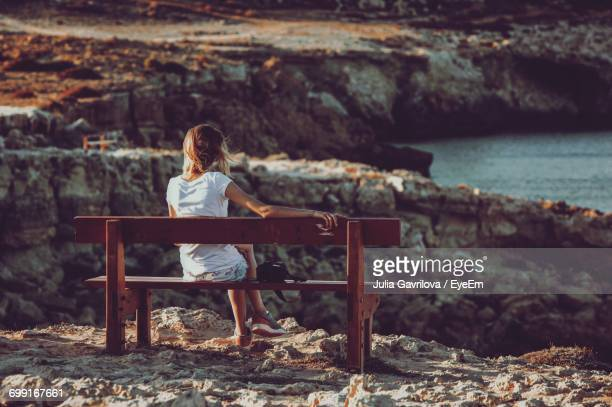 Rear View Of Young Woman Sitting On Rocky Coastline
