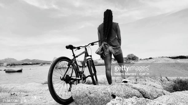 Rear View Of Young Woman Standing By Bicycle On Rock Formation Against Sky