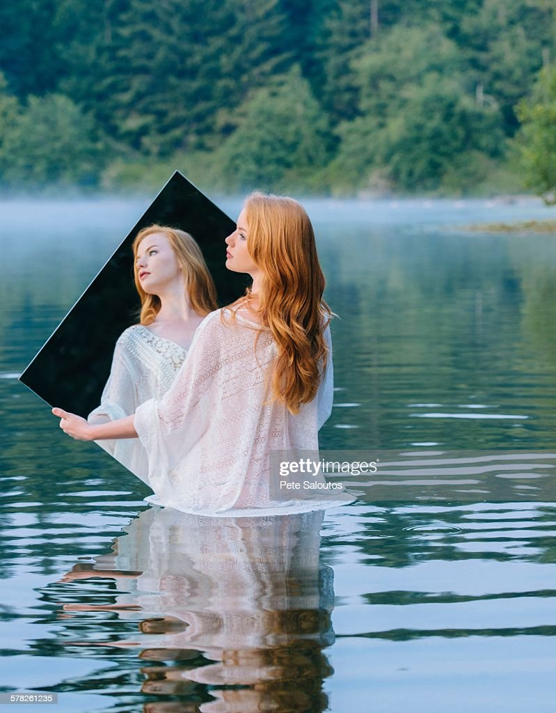 Rear view of young woman standing in lake holding mirror looking away