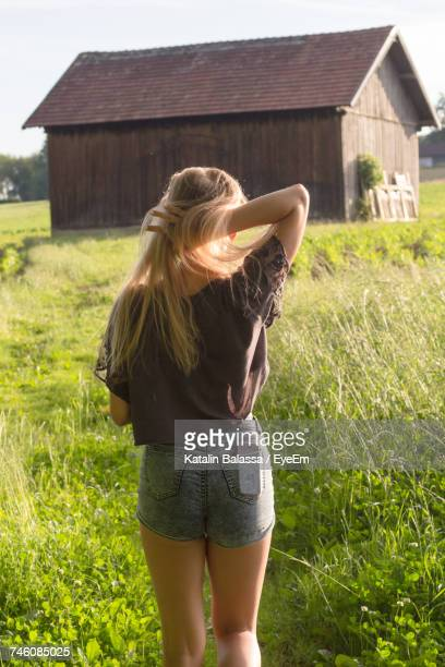 Rear View Of Young Woman Standing On Field