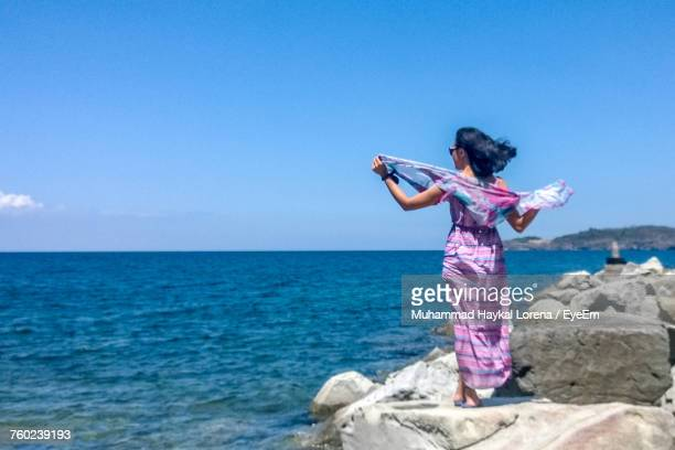 Rear View Of Young Woman Standing On Rock By Sea Against Sky On Sunny Day